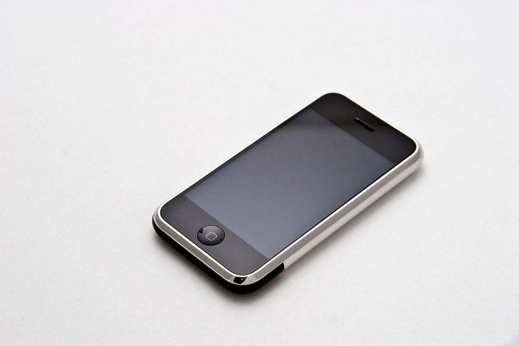 The original iPhone face up on a white table.