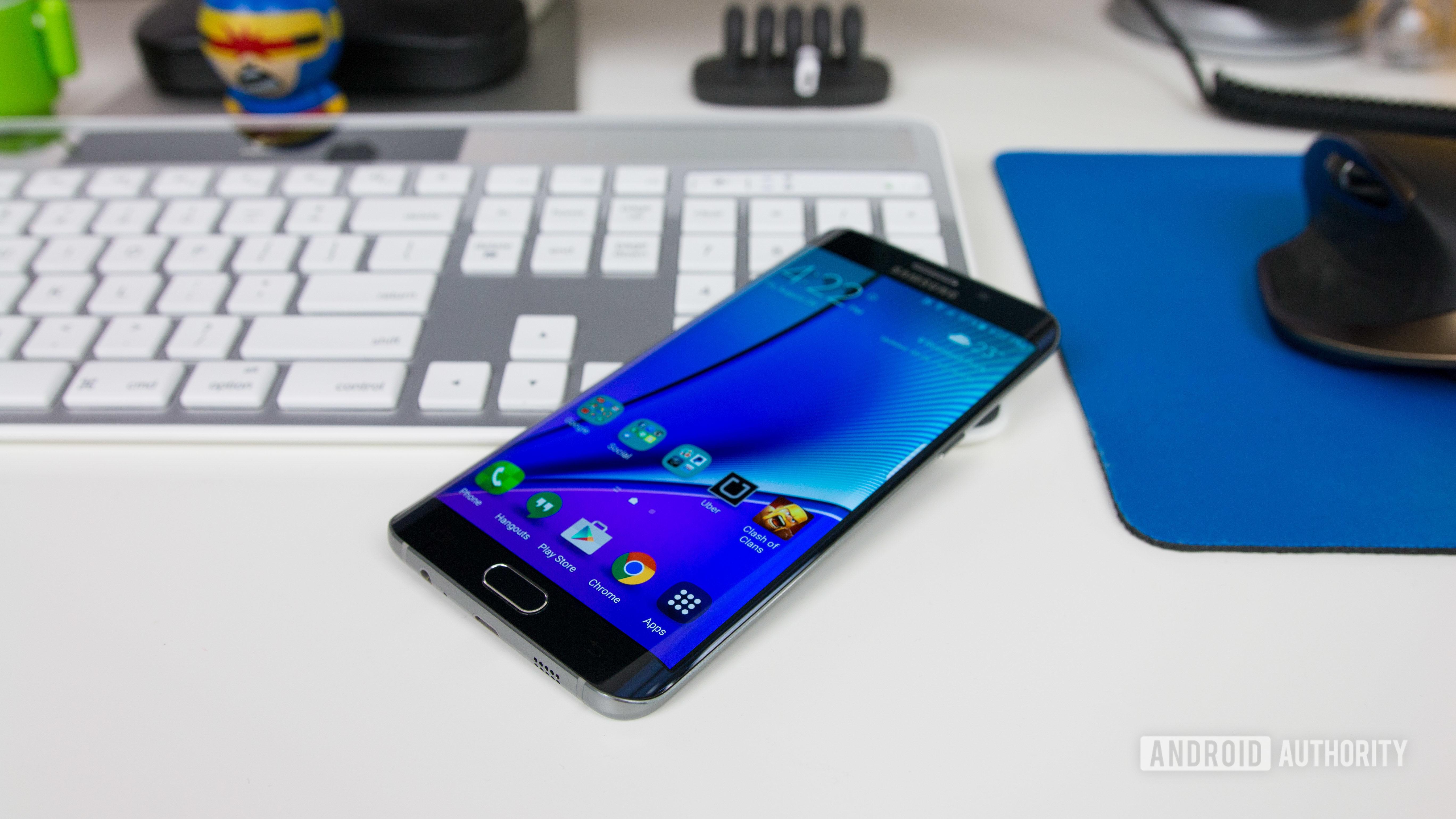 The Samsung Galaxy S6 Edge lying on a silver keyboard.