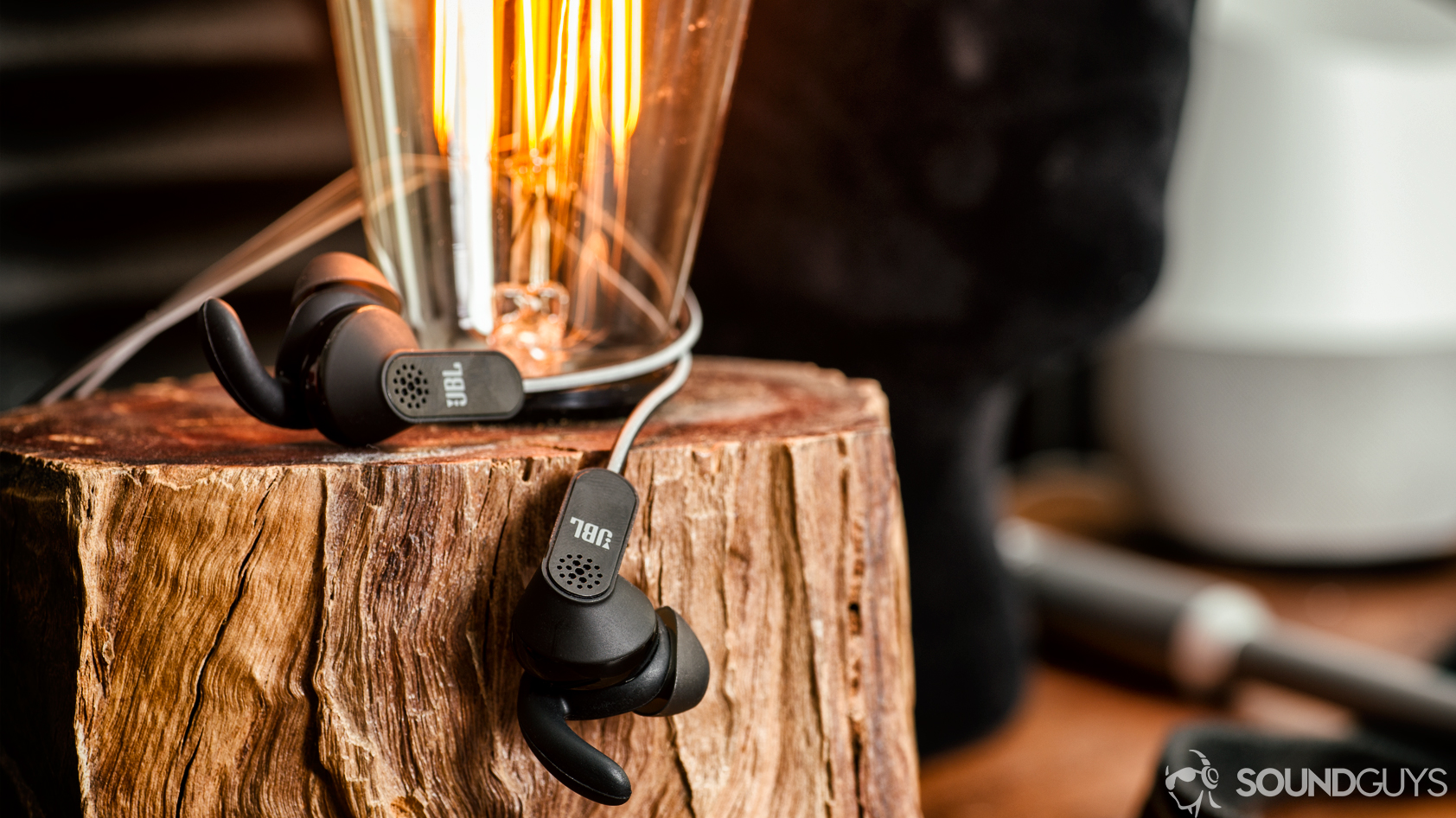 USB-C audio JBL Reflect Aware on a piece of wood with an Edison light bulb sticking out from it.