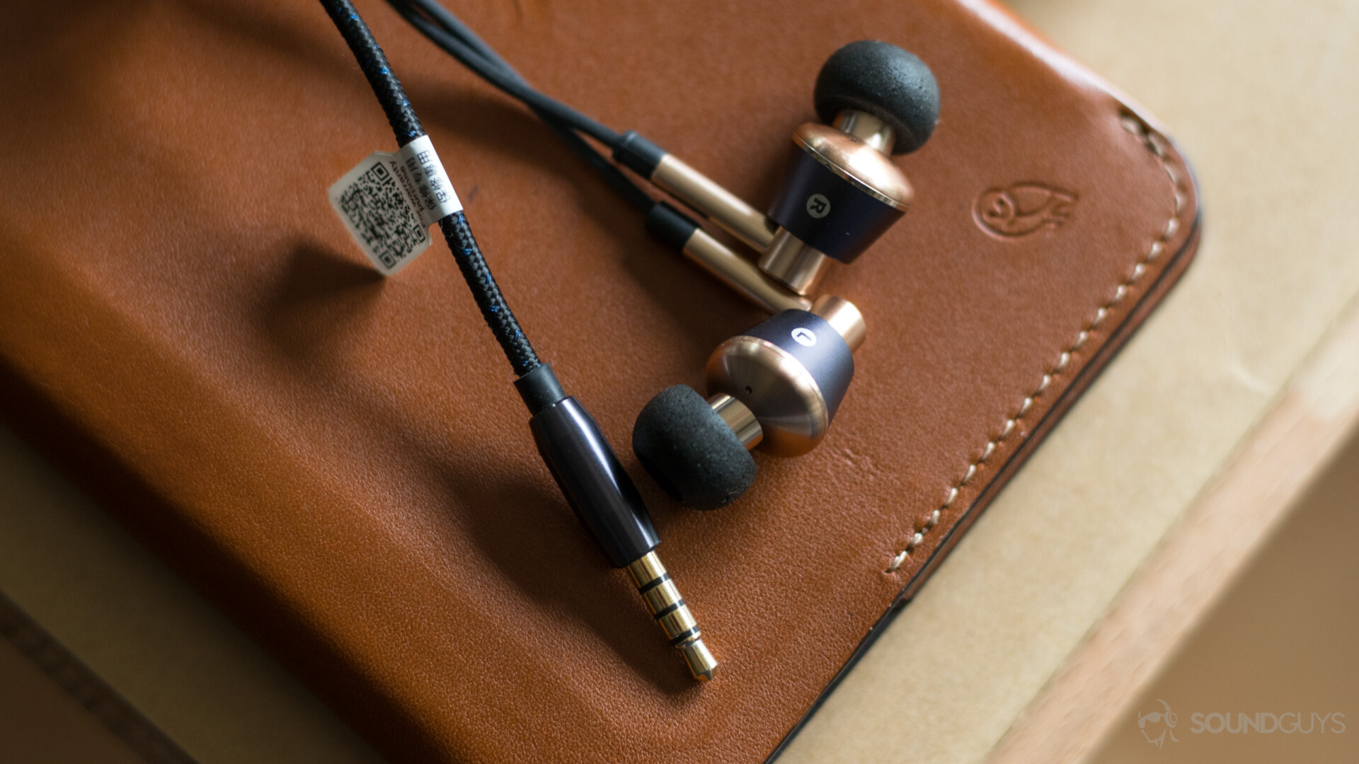 Samsung Galaxy S10 headphone: 1More Triple Driver In-Ear on a leather surface.