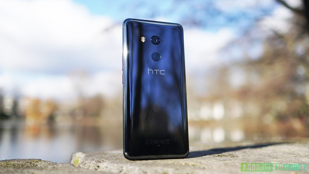 The HTC U11 Plus smartphone on a stone in front of a lake on a sunny day.