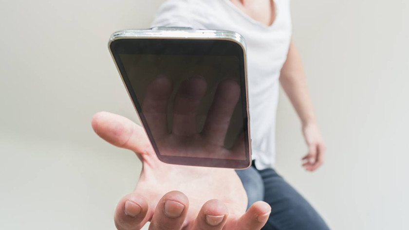 A man almost dropping a smartphone