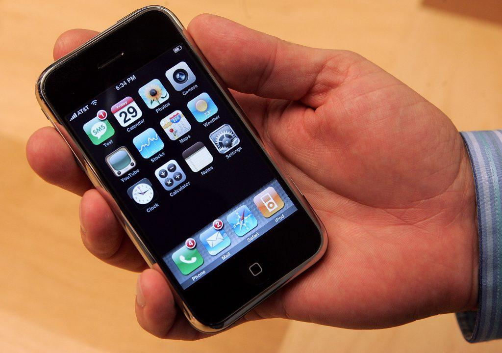 A picture of a hand holding the original Apple iPhone.