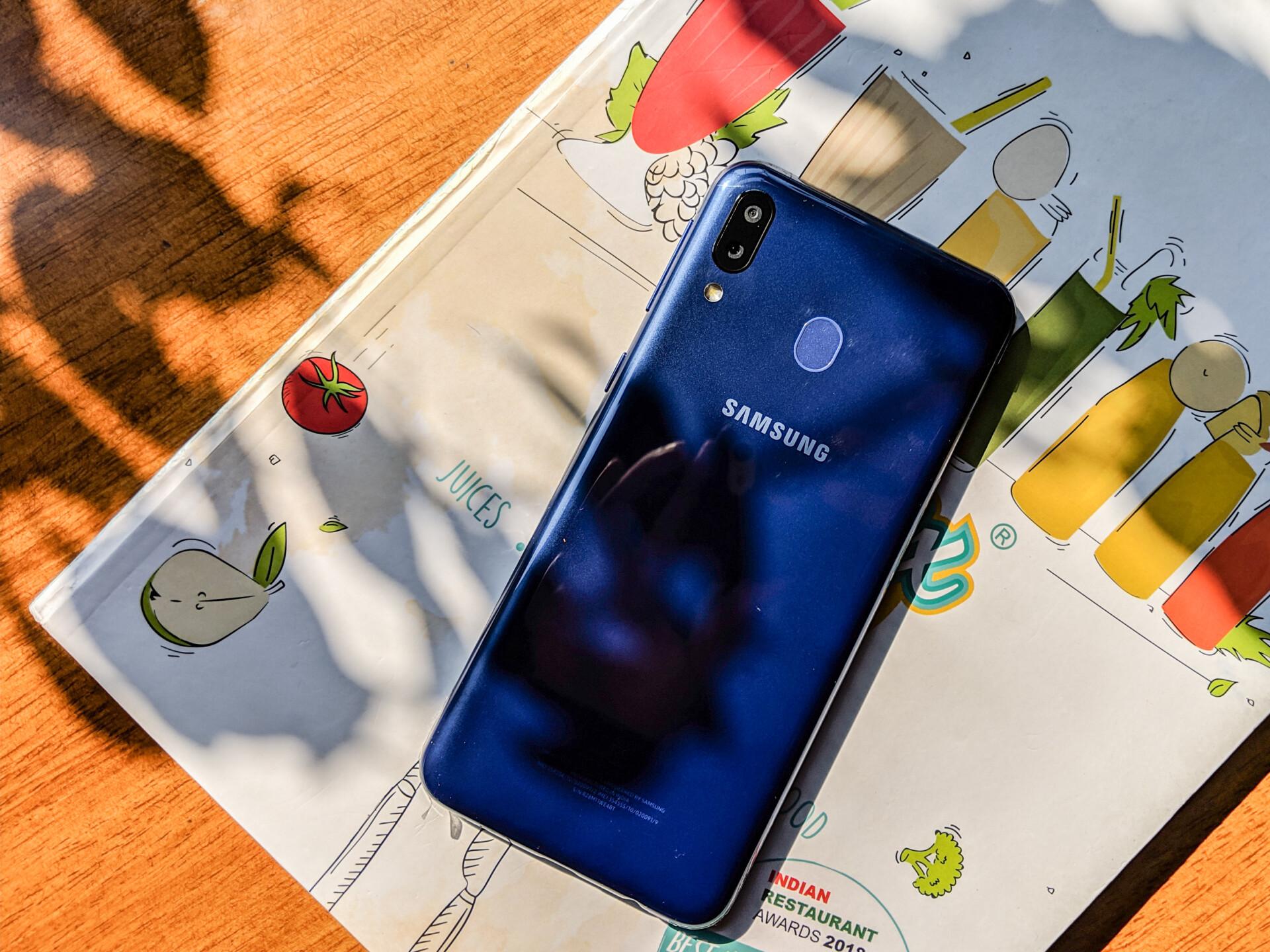 Back side of Samsung Galaxy M20 laying on a magazine.