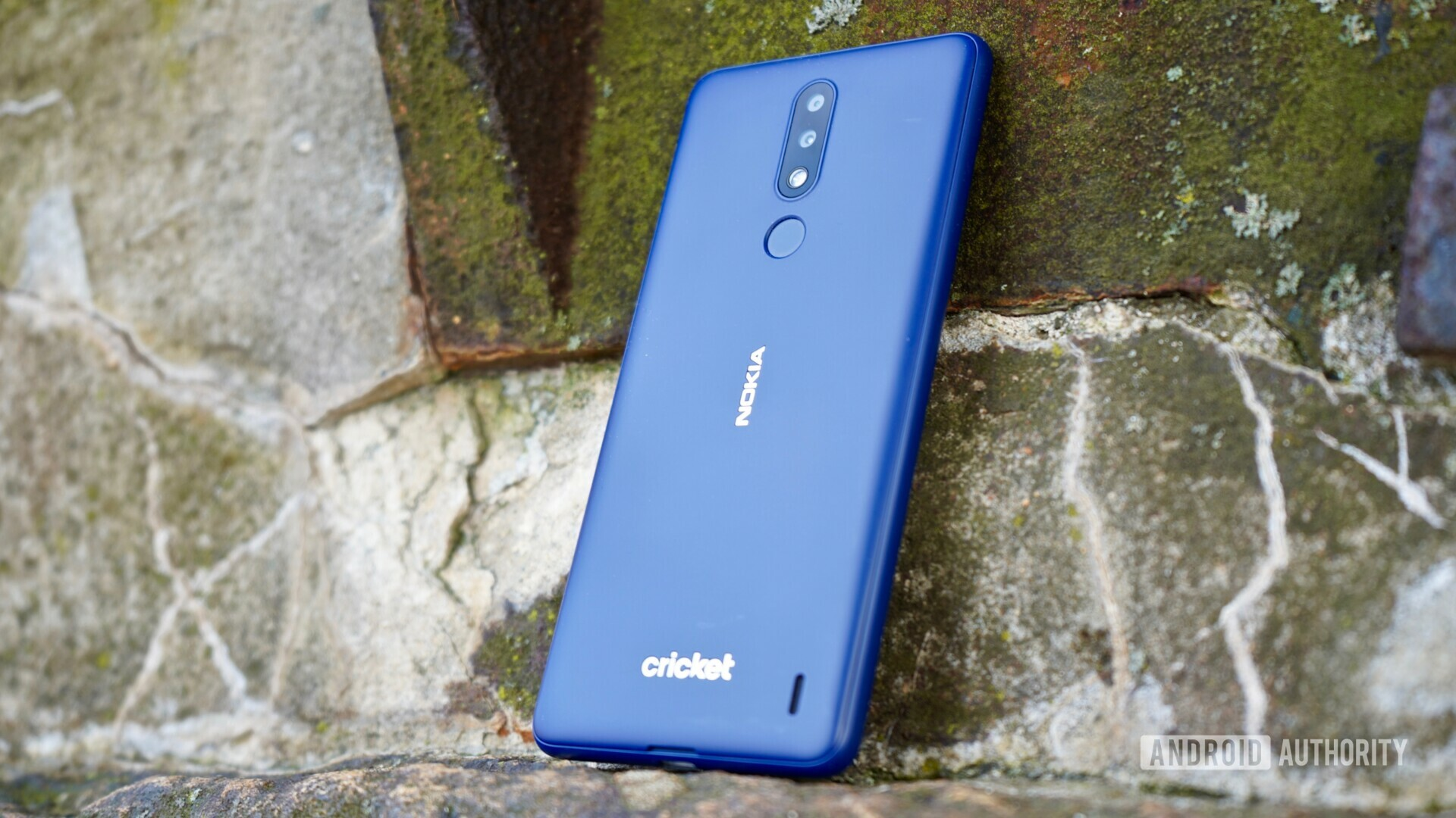 Back side view of the Blue Nokia 3.1 Plus on a stone.