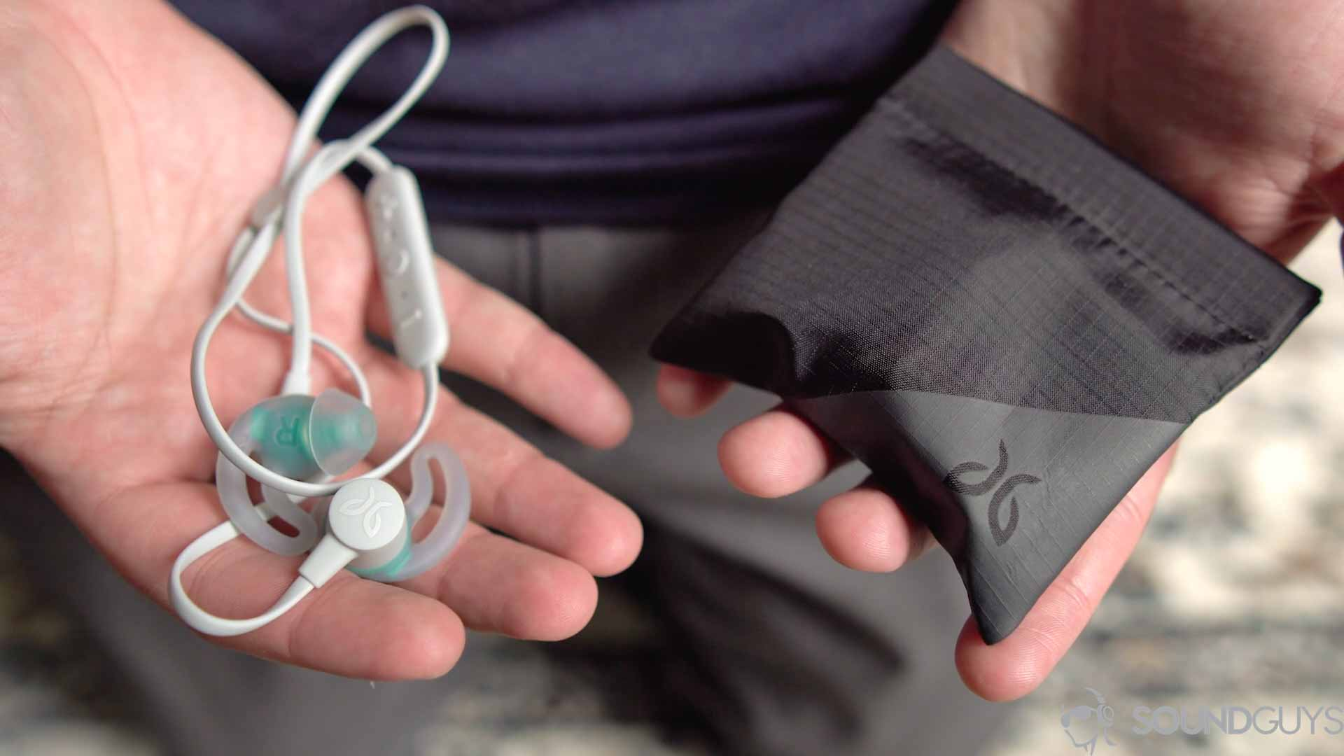 Samsung Galaxy S10 headphone: Jaybird Tarah with carrying pouch held by man.