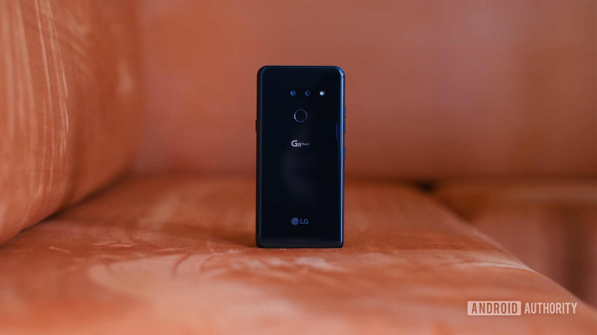 Backside of a black LG G8 ThinQ on a red soffa.