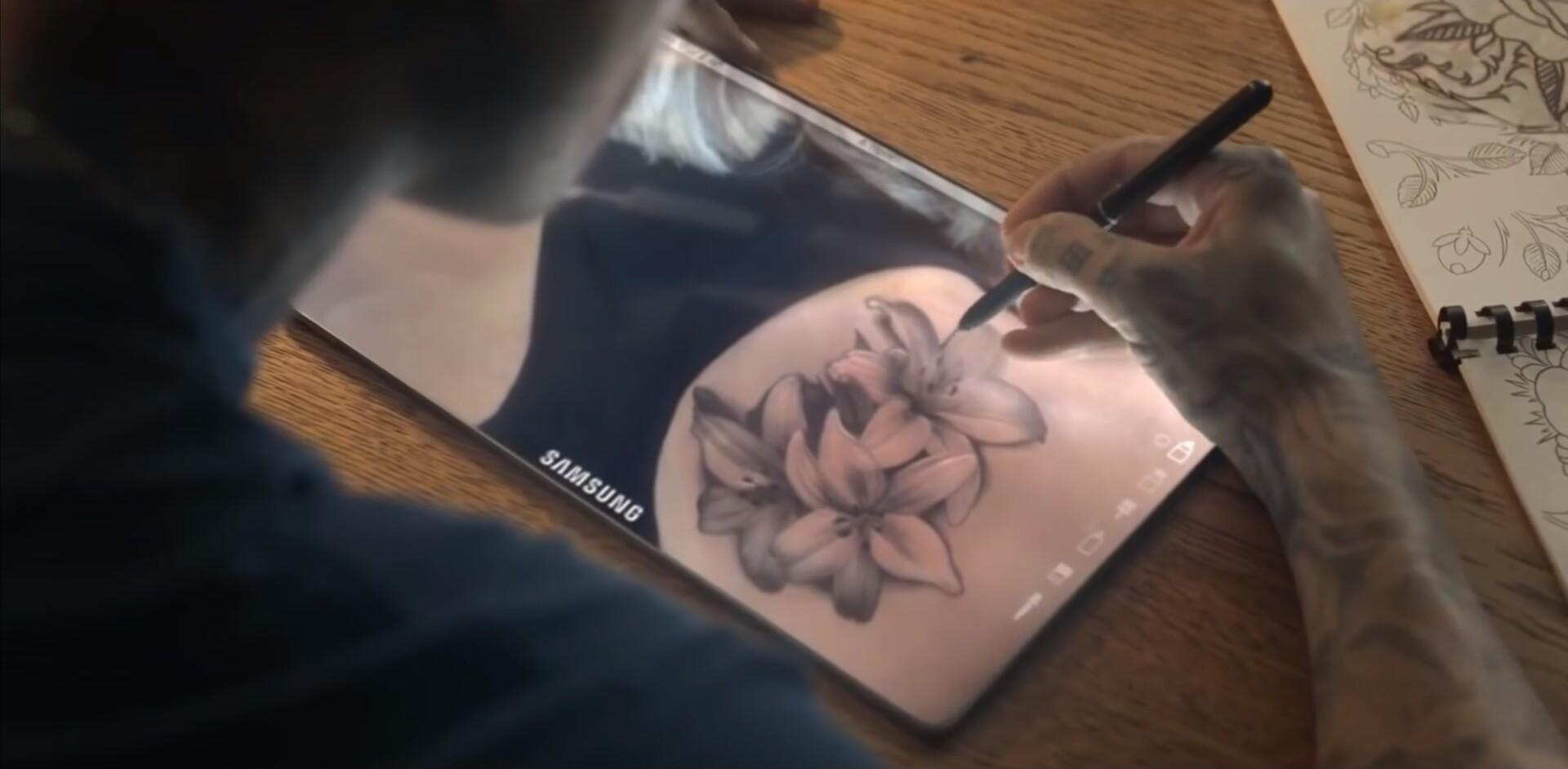 A tattoo artist drawing on a bezel-less tablet
