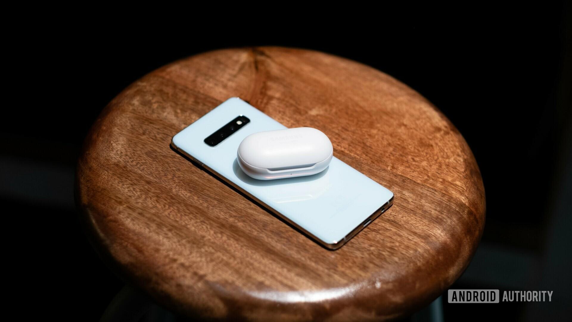 Samsung Galaxy Buds sitting on a white Galaxy S10.