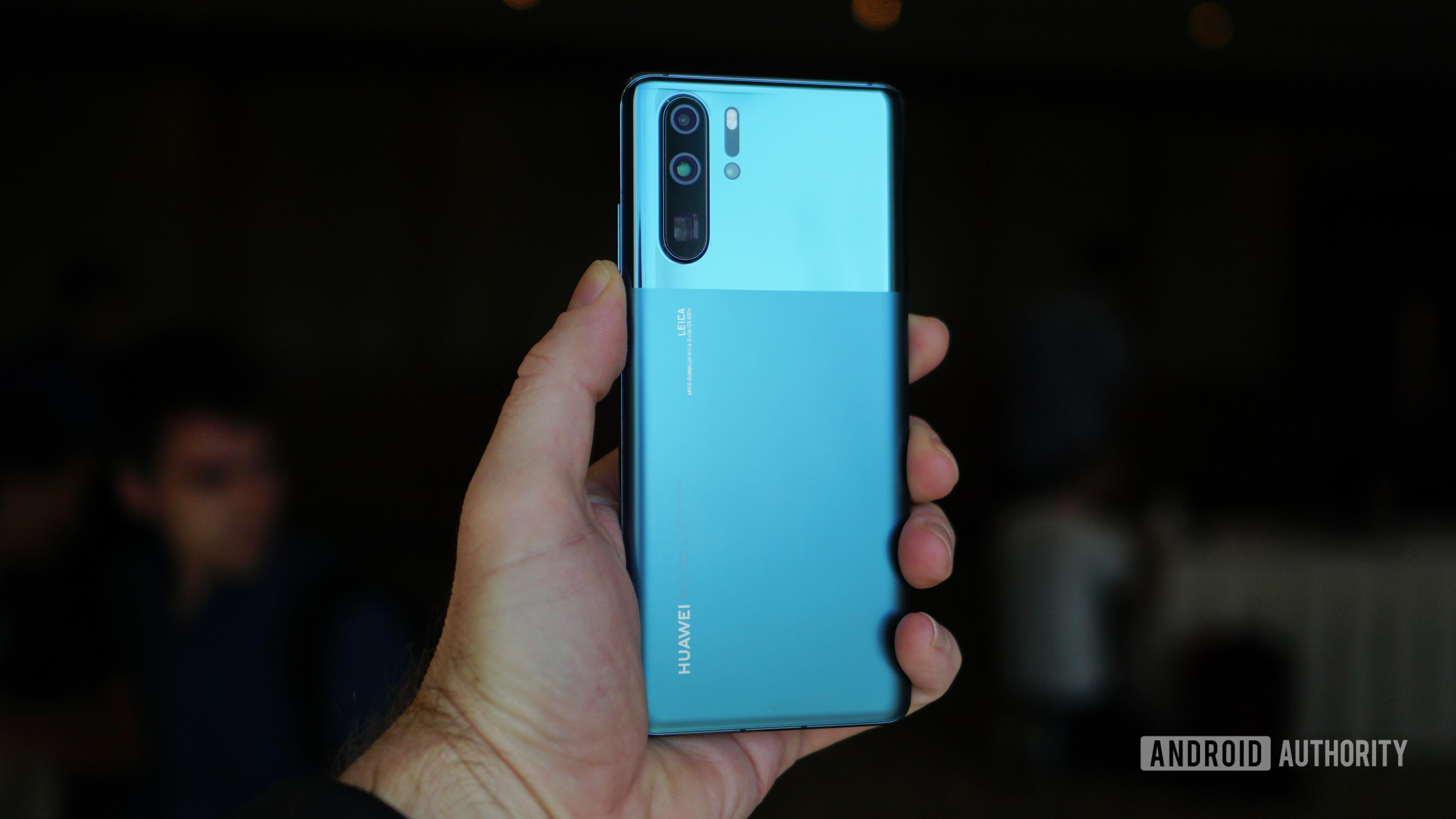 Huawei P30 Pro in misty blue in hand dark barckground