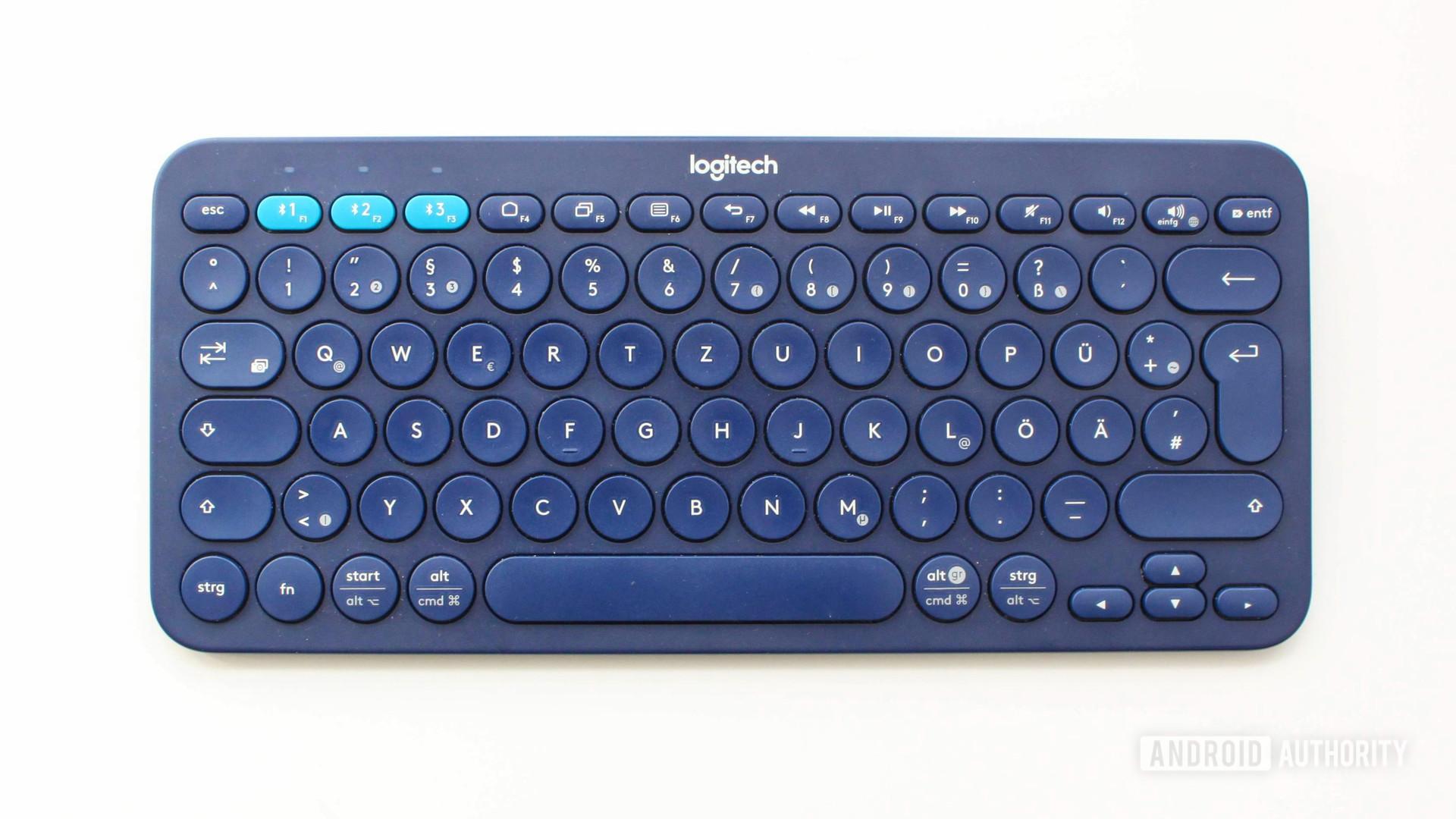 A logitech k380 keyboard in blue on a white table
