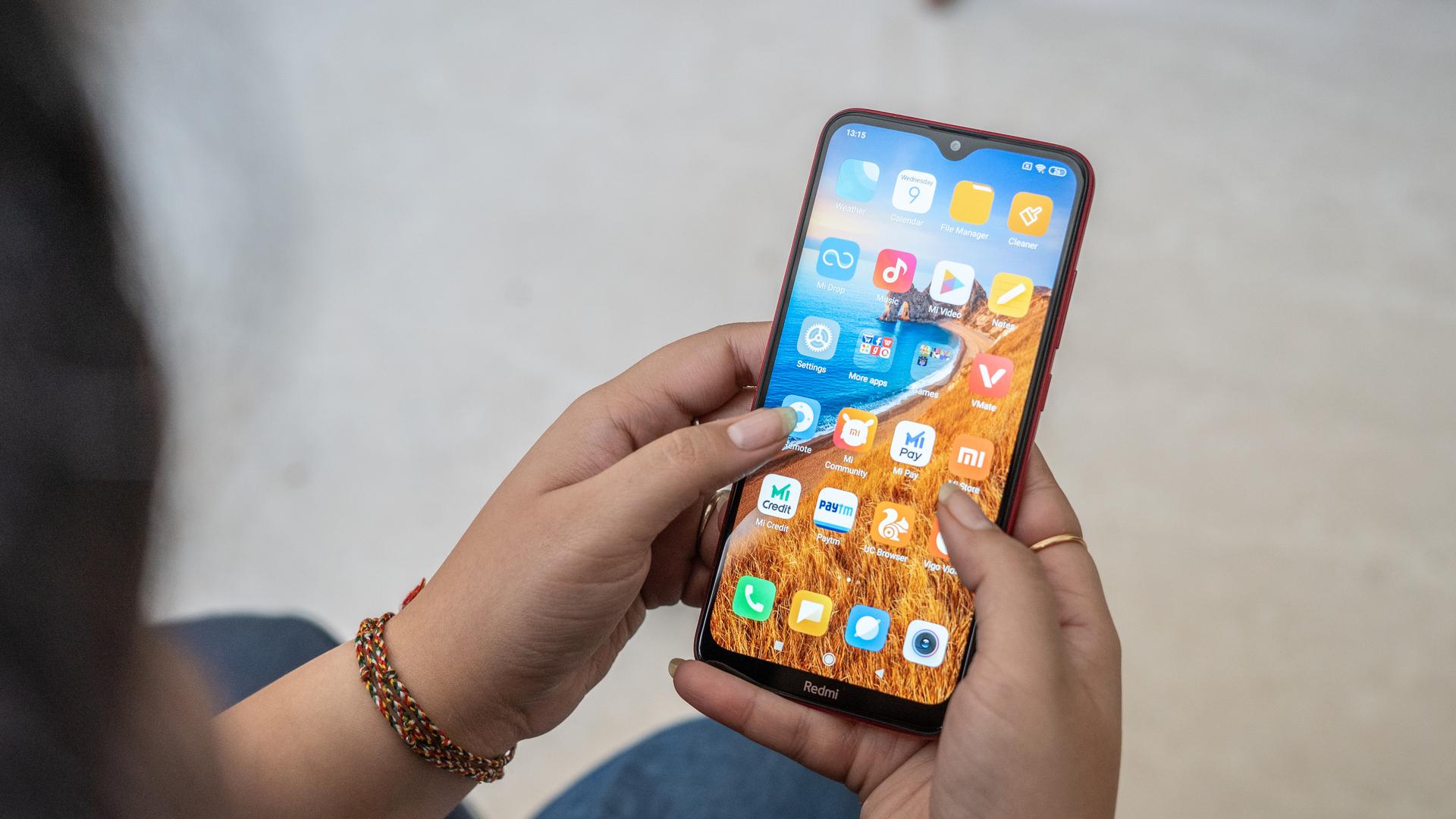 Redmi 8 in hand showing homescreen