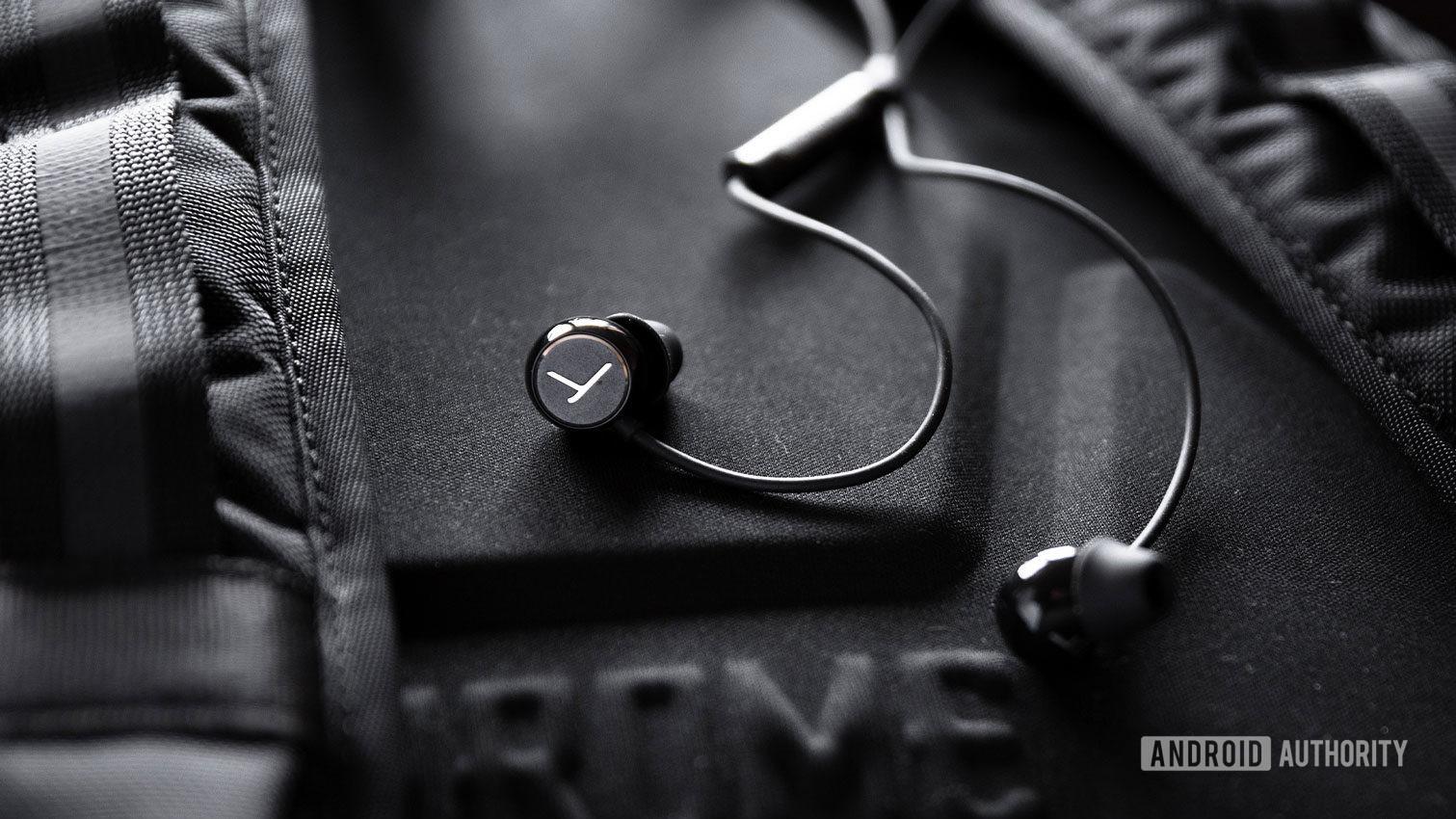 The Beyerdynamic Soul Byrd wired earphones in black against a black backpack.
