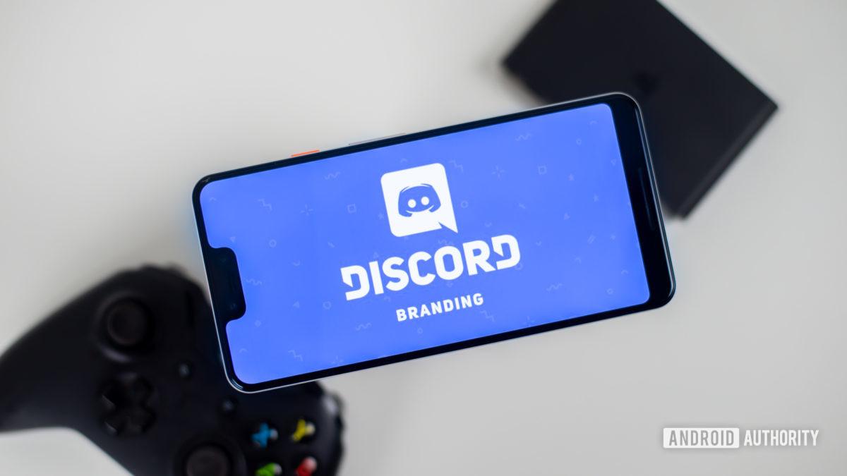 Discord on smartphone next to gamepad stock photo 1