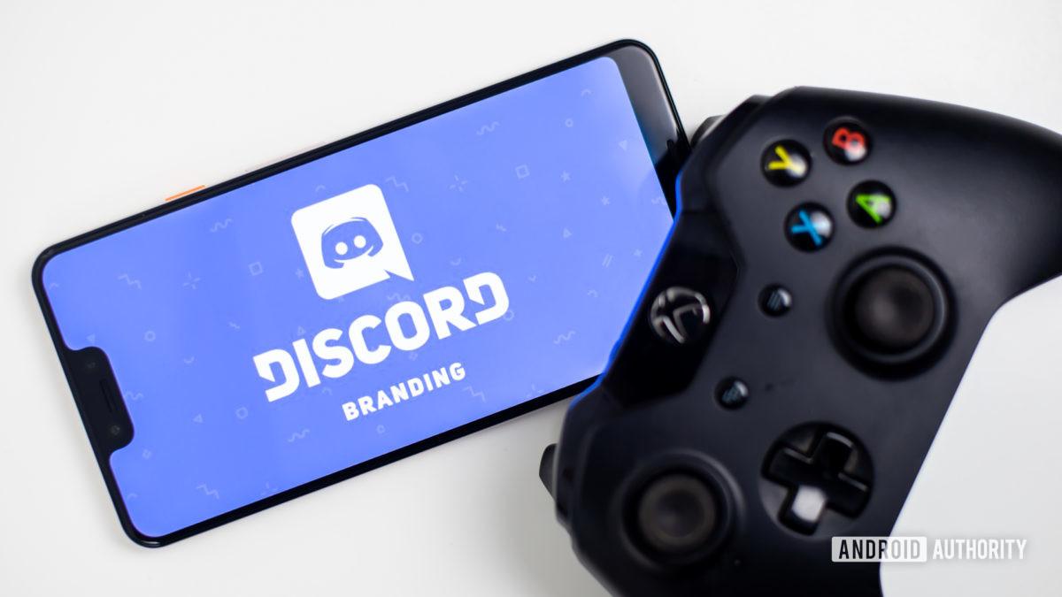 Discord on smartphone next to gamepad stock photo 3