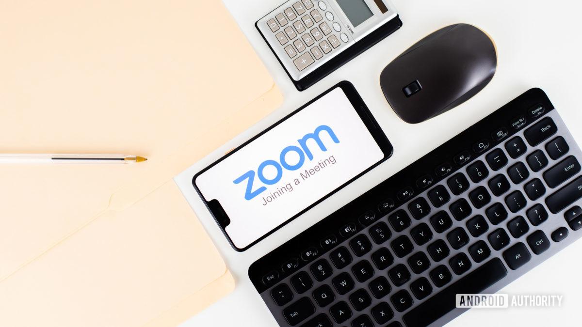 Zoom Meetings on smartphone next to office equipment stock 2 - Zoom vs Skype