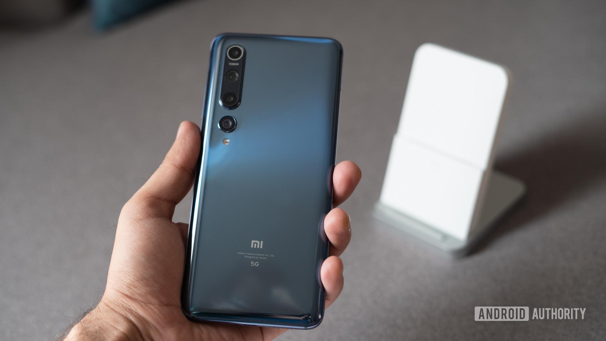Xiaomi Mi 10 in hand with charging dock