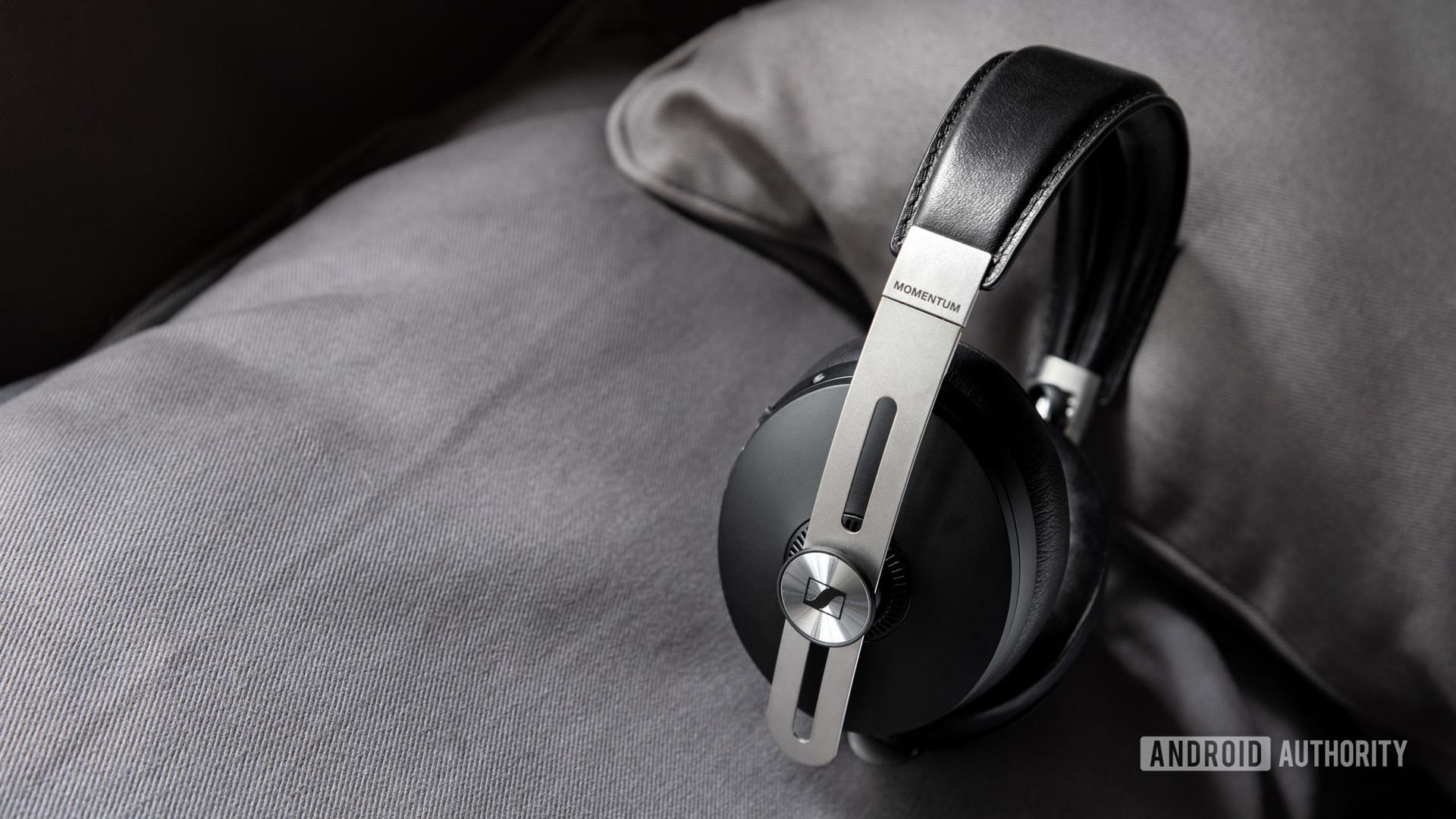 The Sennheiser Momentum Wireless 3 Bluetooth headphones in black rest against a gray surface.