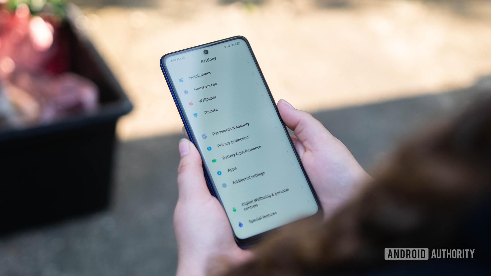Xiaomi Poco X3 NFC settings menu held in the hand