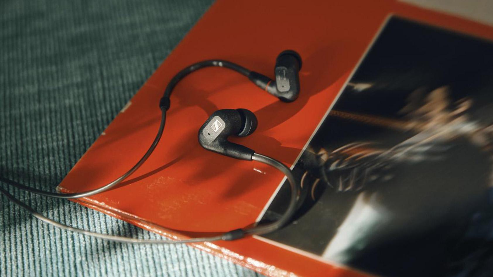 The Sennheiser IE 300 earbuds against a magazine.