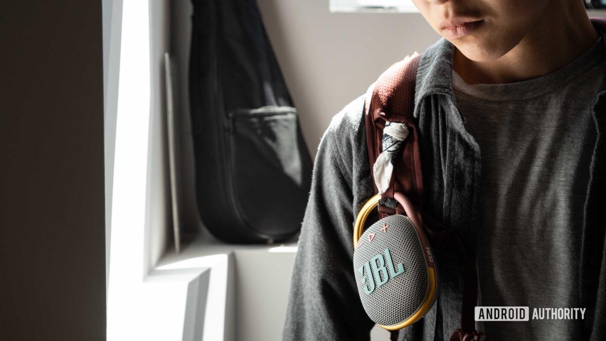 A woman wears the JBL Clip 4 speaker on her backpack strap.