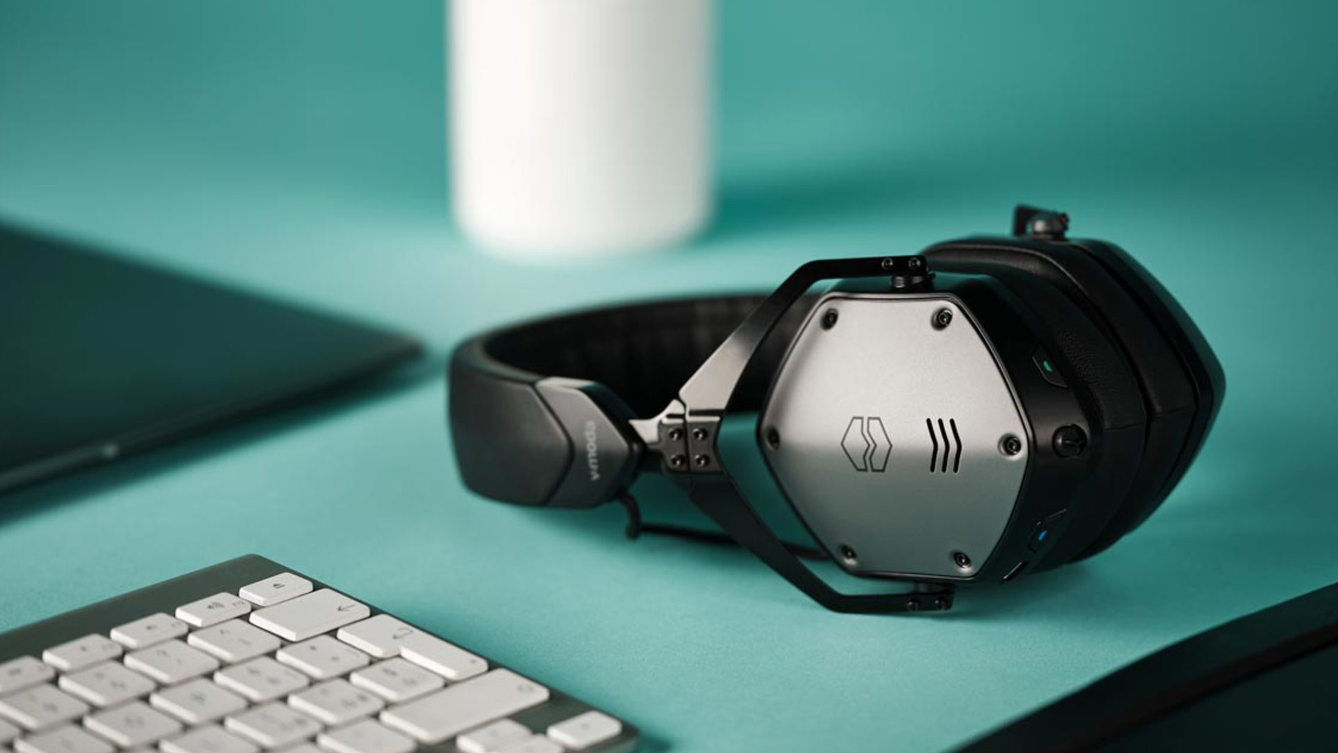 V MODA M-200 ANC on a teal desk next to keyboard