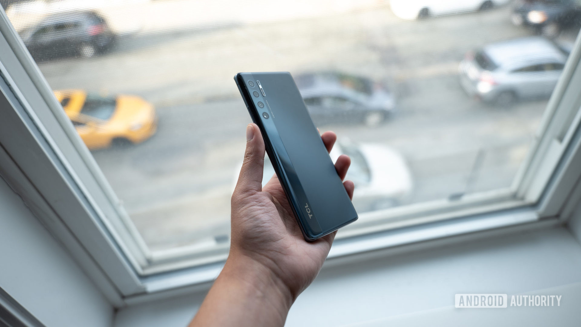 A person holding the TCL 20 Pro in their hand, in front of a window, with the back of the phone visible.