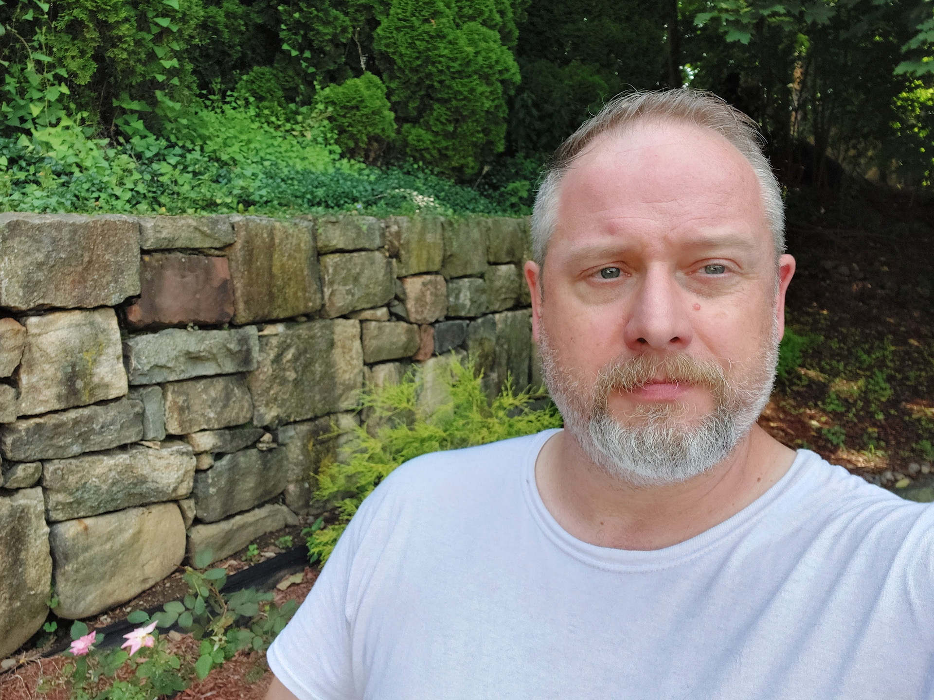 Samsung Galaxy A42 photo sample selfie taken outdoors of a man with a beard in a white t-shirt with a wall and greenery behind him