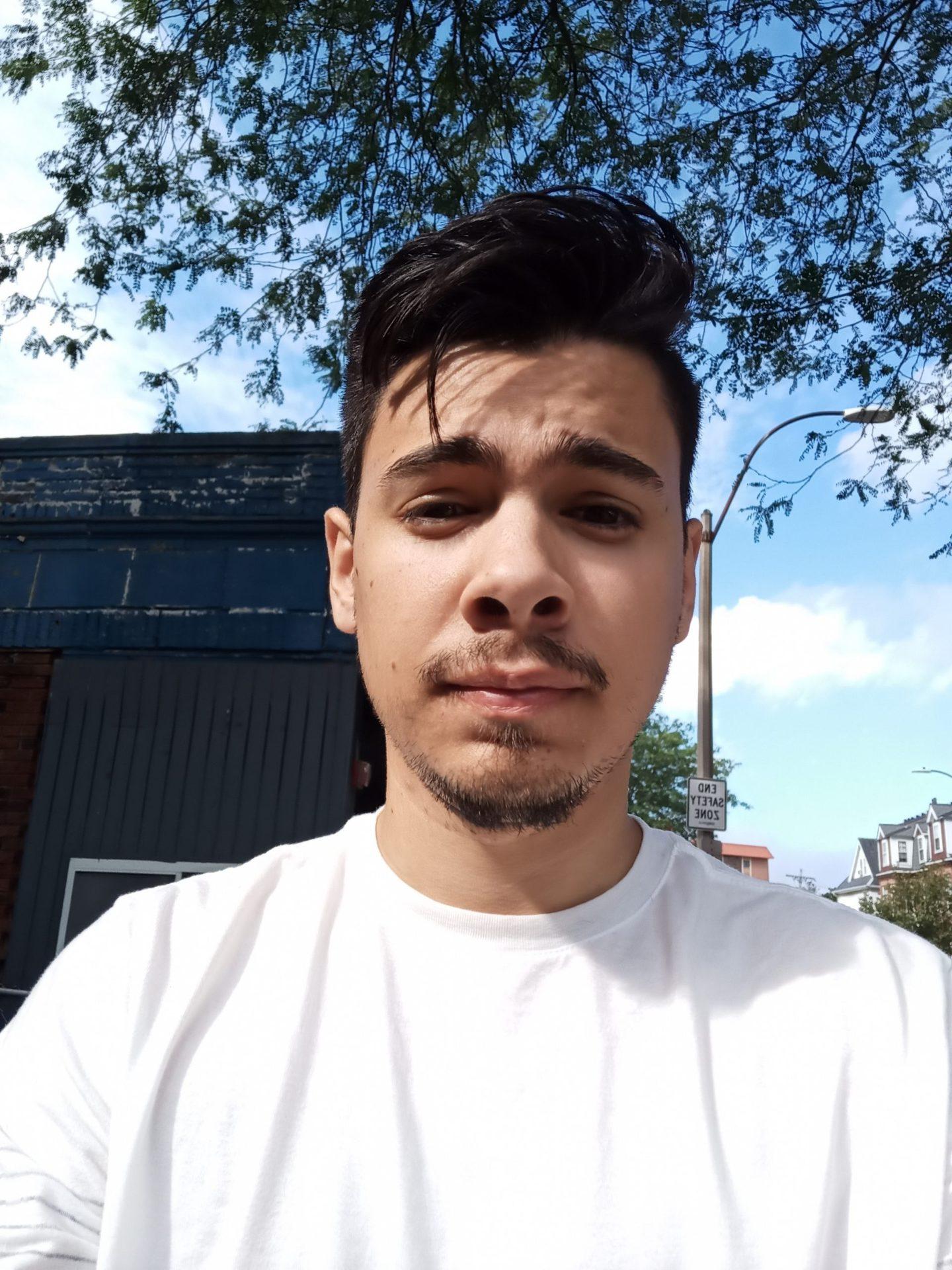Selfie photo of man outdoors with dark hair and beard, wearing a white t-shirt taken on Blu G91 Pro