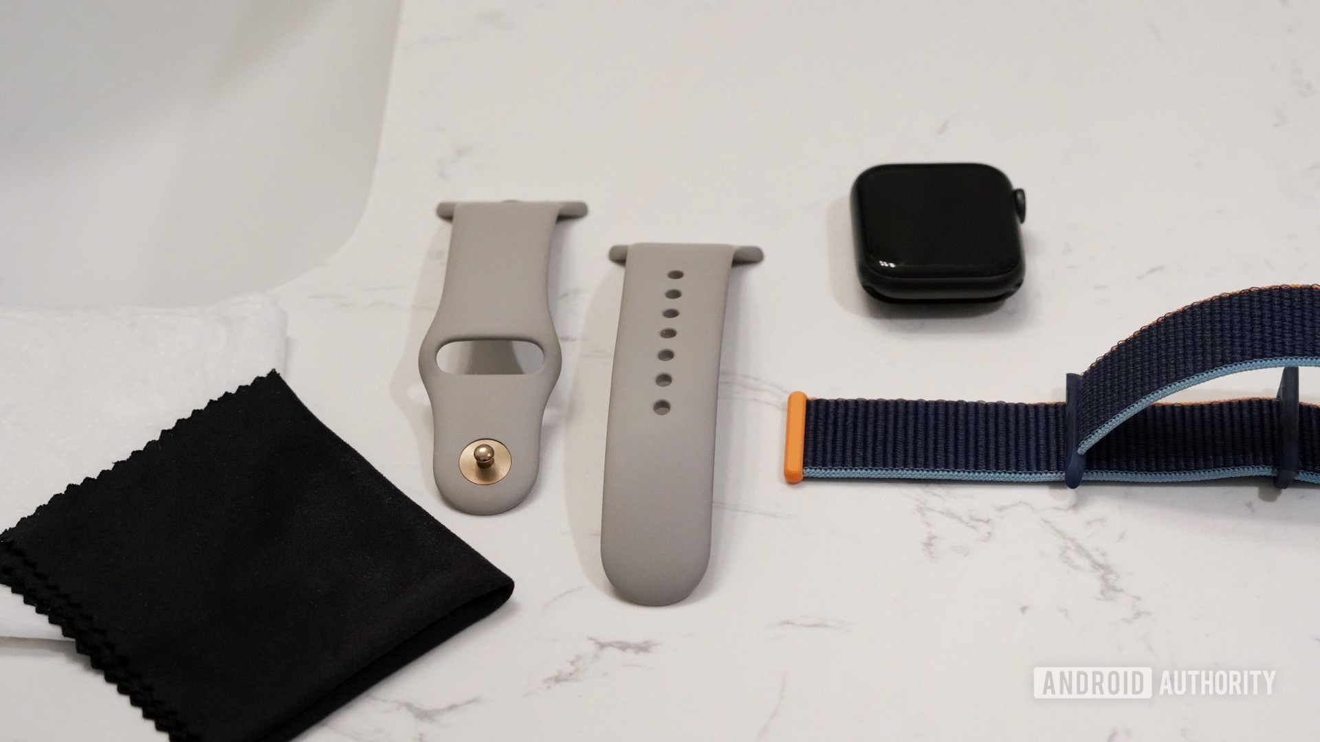 Apple Watch Series 6 and two bands rest on a bathroom counter along with clothes need to clean Apple Watch bands