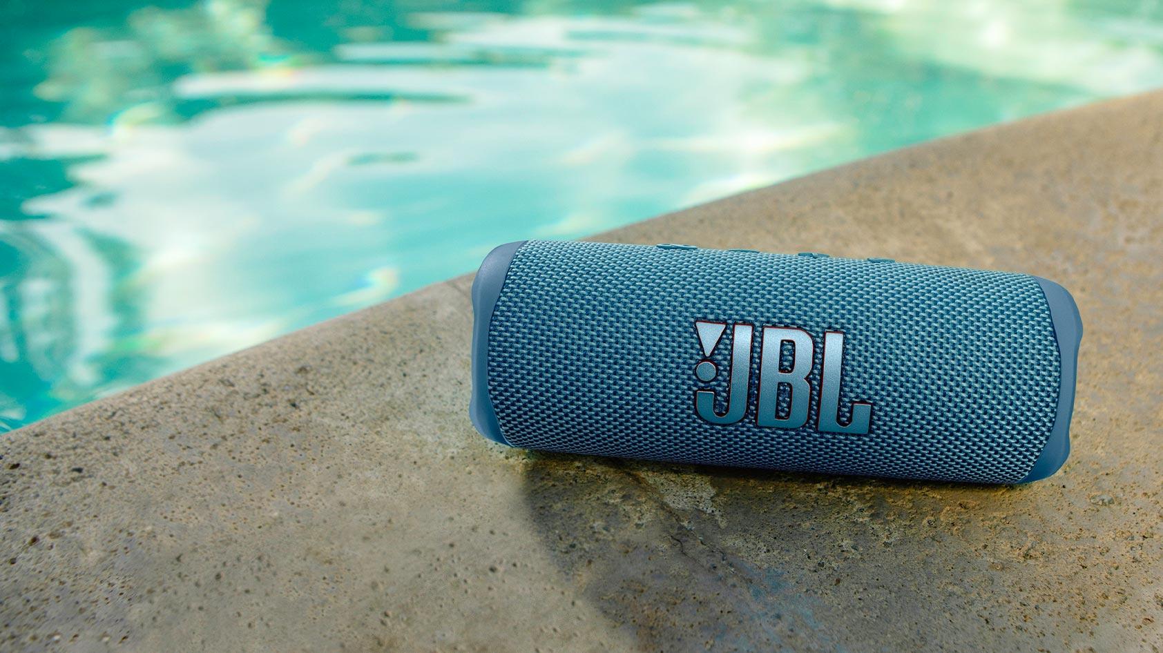 The JBL Flip 6 in blue rests poolside.