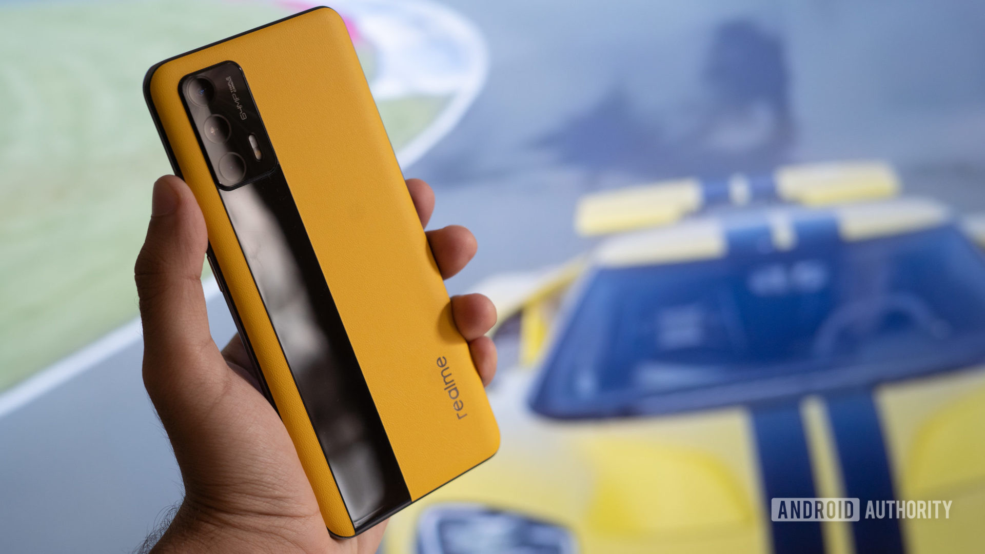 Realme GT in hand with race car behind it.