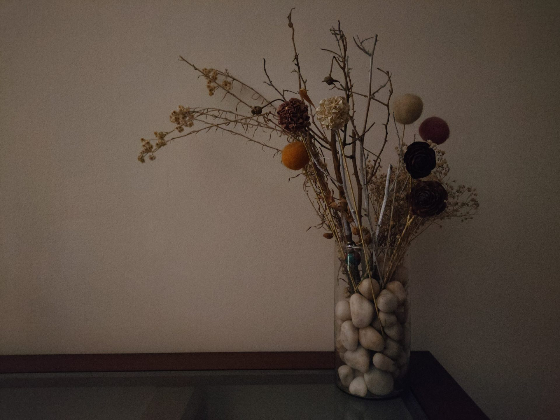 Realme GT low light shot of dried grasses and flowers in a vase with pebbles.