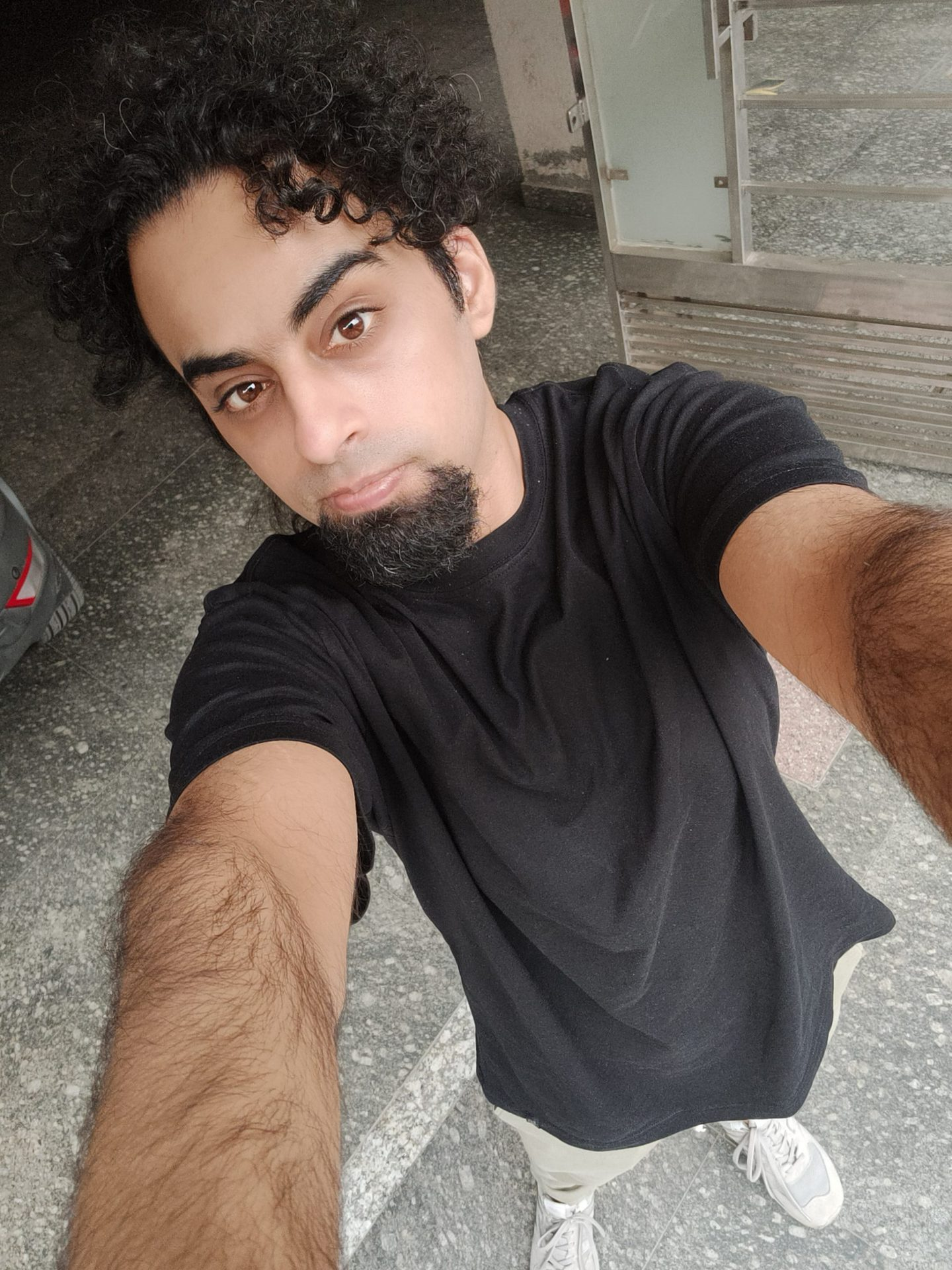 Realme GT selfie sample shot of a man with dark curly hair and a beard, wearing a black t-shirt.