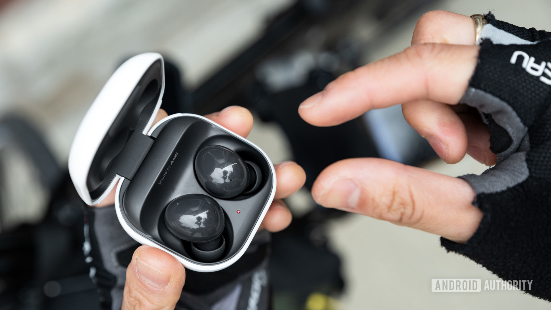 A hand reaches to remove one Samsung Galaxy Buds 2 noise cancelling true wireless 2 earbud from the case.