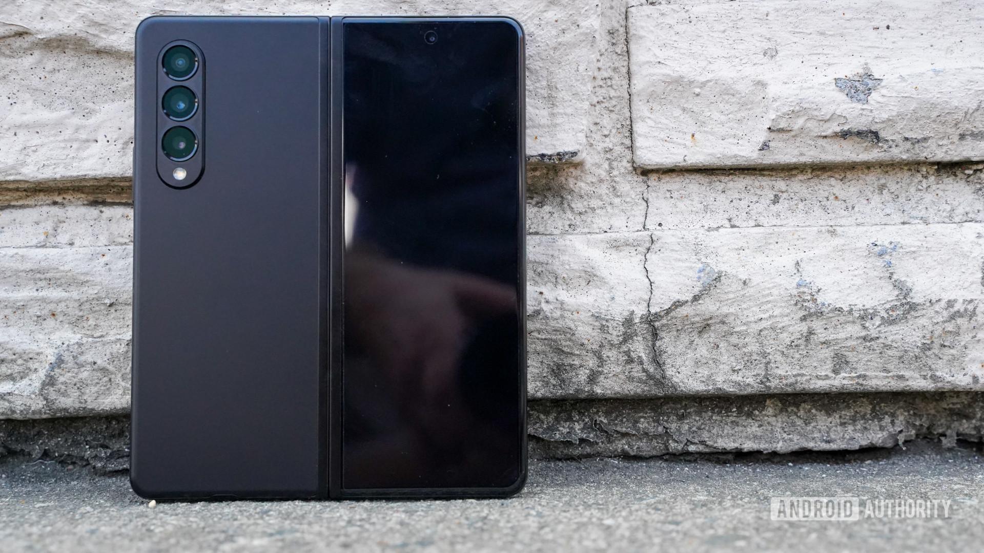 Samsung Galaxy Z Fold 3 open rear view showing camera module, against a brick wall.