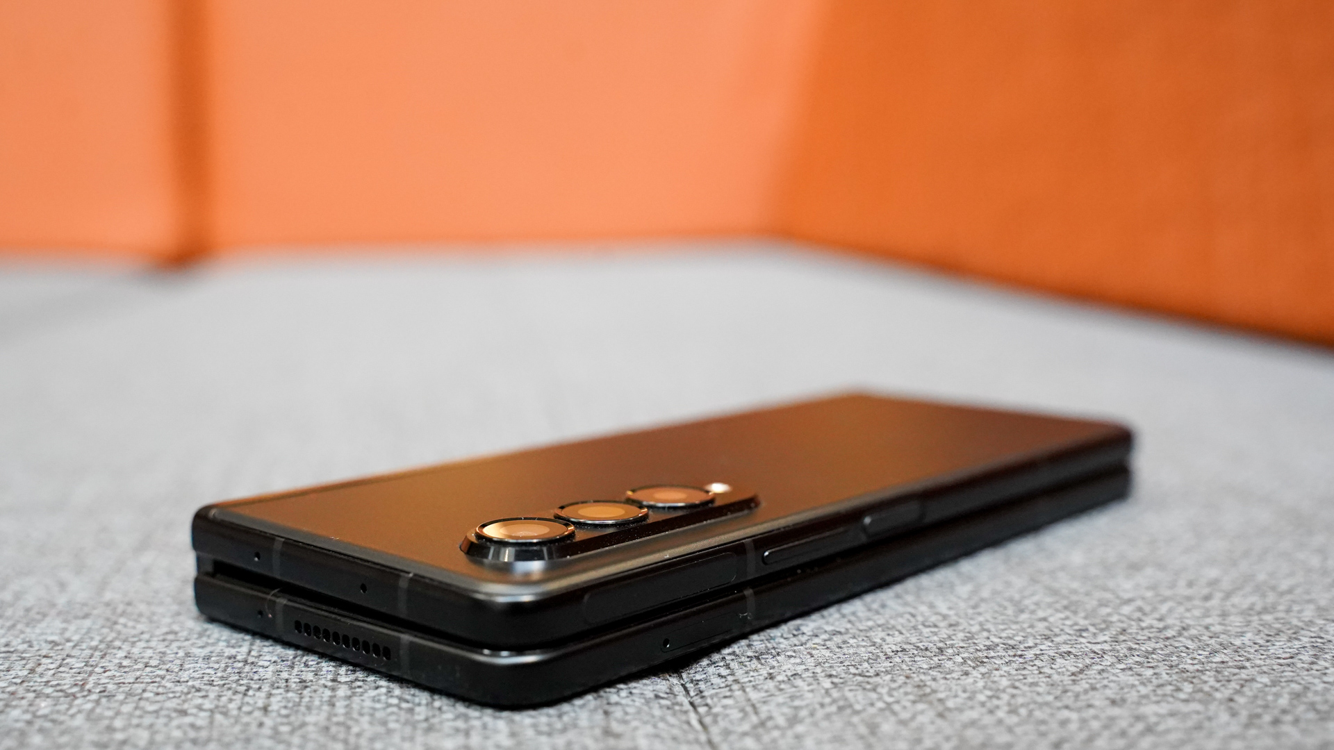 Samsung Galaxy Z Fold 3 top right corner closed on a couch.