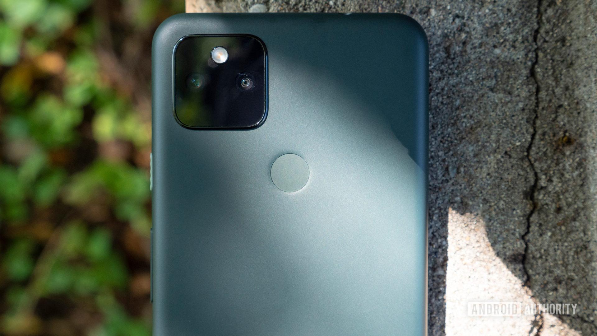 google pixel 5a pada sepotong semen menunjukkan punggungnya sebagian besar berwarna hitam dengan kamera close up
