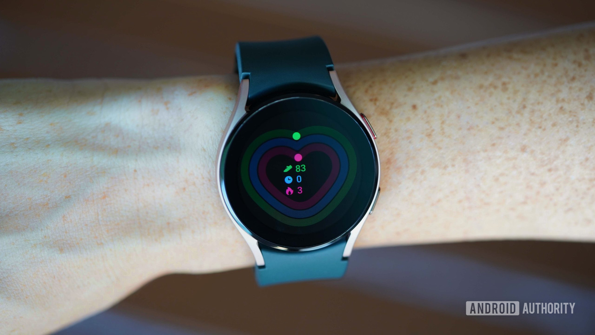A Galaxy Watch 4 displays the Daily Activity screen hovering over a brown picnic table.