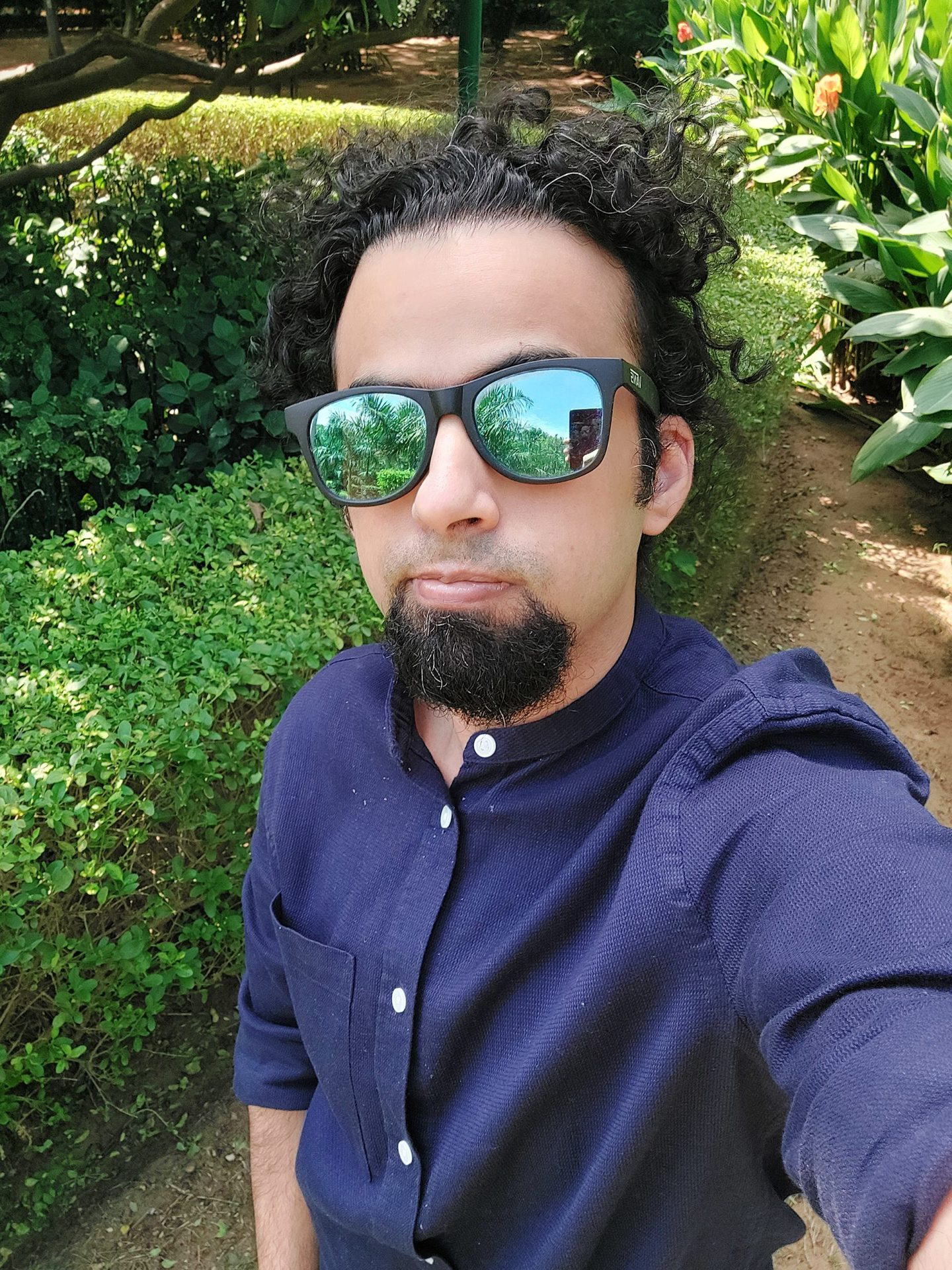 Samsung Galaxy A52s 5G selfie camera standard shot of man with dark hair and beard wearing a blue long-sleeve shirt and mirrored shades, taken outdoors next to a green hedge.