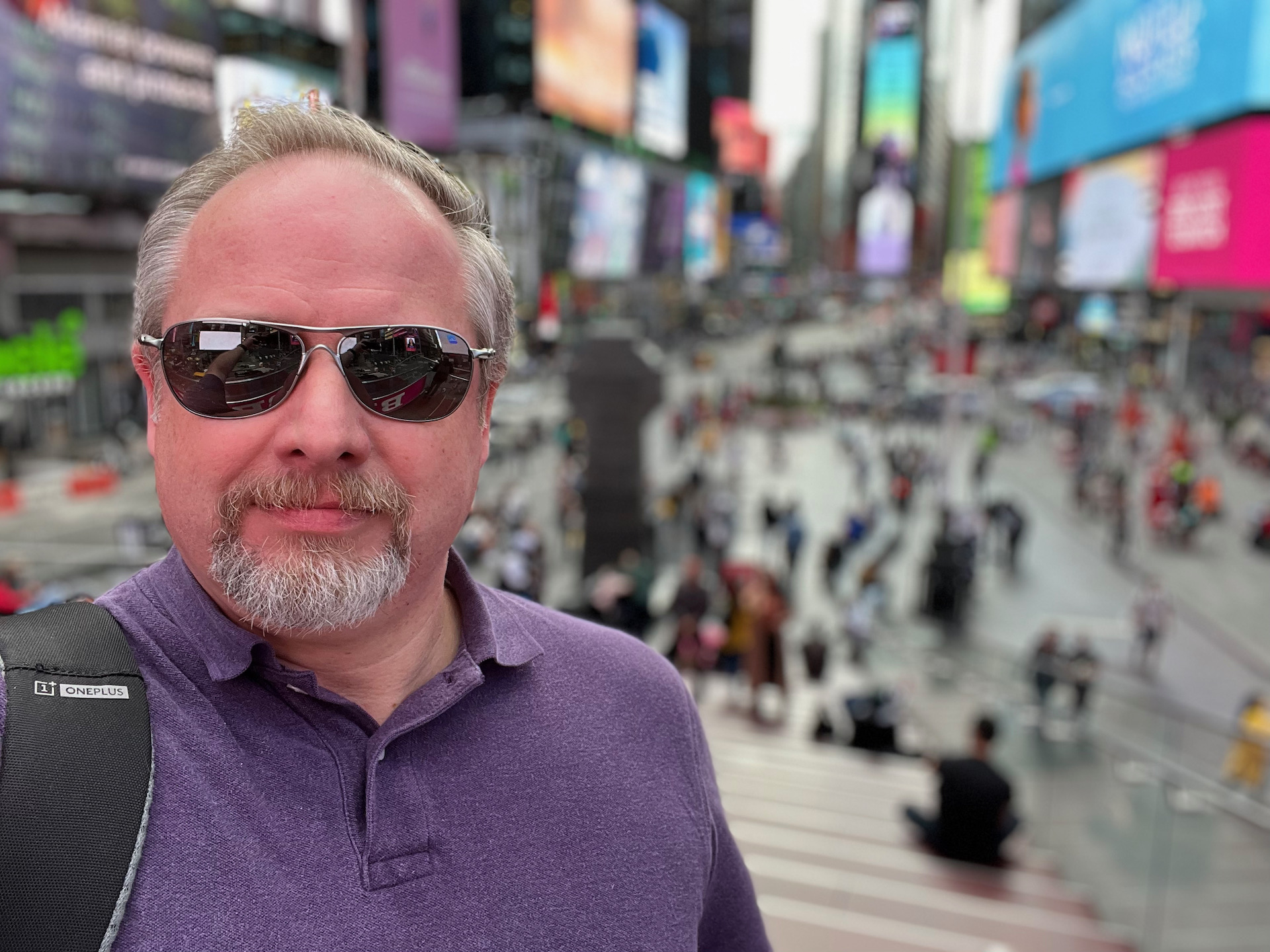 Apple iPhone 13 photo sample Times Square portrait of a man with light colored hair and beard wearing a purple top and black shades