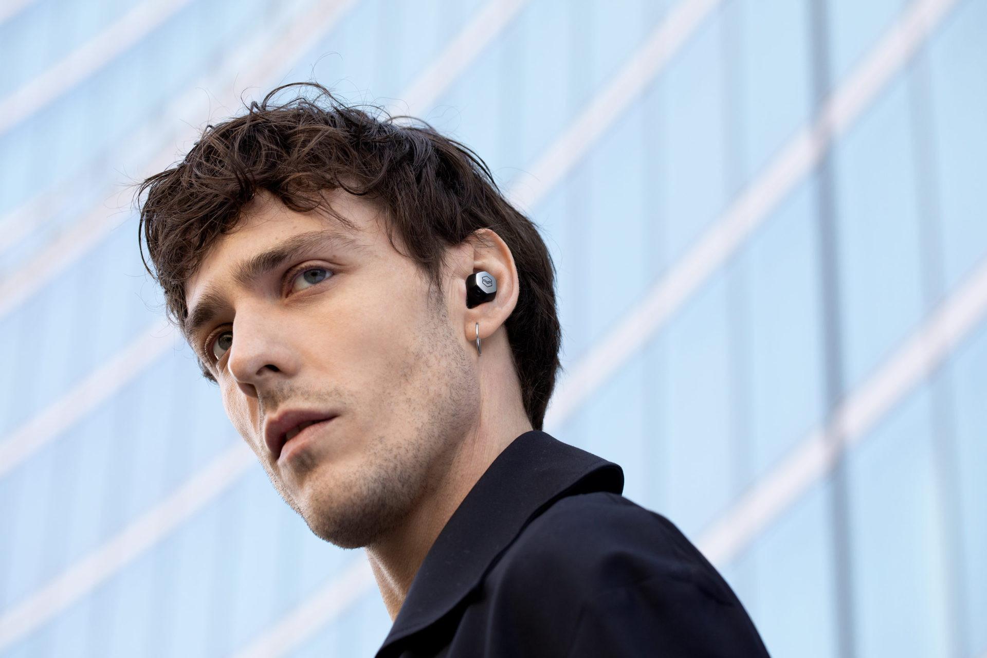 Une personne masculine porte le v-moda Hexamove Pro en noir avec le bouclier personnalisé argenté installé.